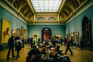 People sitting and looking at paintings in a museum