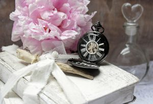 Vintage watch, flowers and glass bottle on the table.