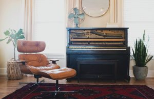 piano next to a chair inside the room