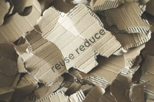 Pieces of cardboard with words reuse reduce written on one of them.