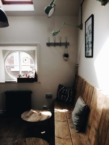 Renting vs buying a home in NYC. Wooden sitting area, window, table.