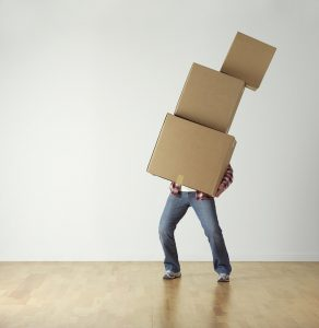 a person carrying too many boxes without the help of Park Slope movers.