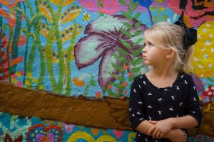 little girl standing against the wall