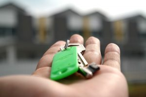 a person holding the keys to his home in one of the most affordable Manhattan neighborhoods