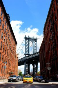 Two buildings and view of Brooklyn bridge between