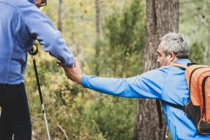 Two seniors helping each other on a forest trail