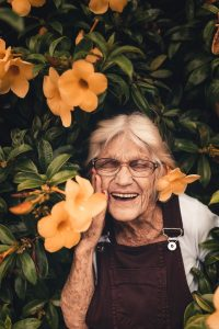 Elderly woman smiling among flowers