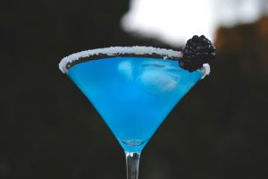 Blue cocktail in martini glass with a blackberry on the rim of the glass, black background