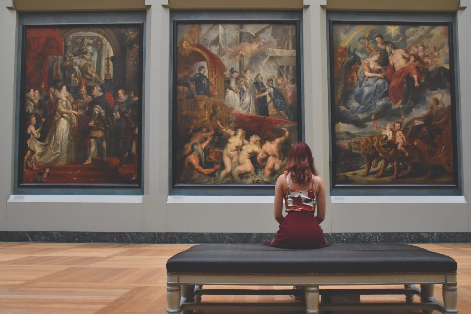 a girl sitting in front of the pictures