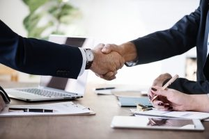 Two men shaking hands. Hiring a moving broker may result in lowered prices on your move.