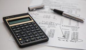 a calculator next to a pen