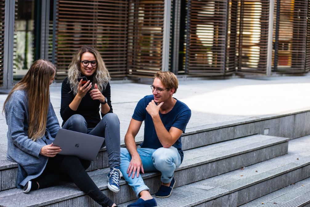 Three people talking outside an apartment building. Meeting new neighbors is a great way to make new friends in your new town quickly.