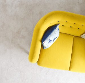 a yellow sofa with a blue pillow