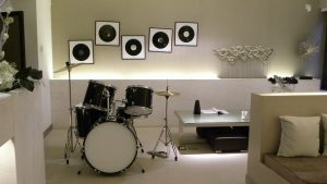 Drums, a coffee table and a sofa in a basement-like white room