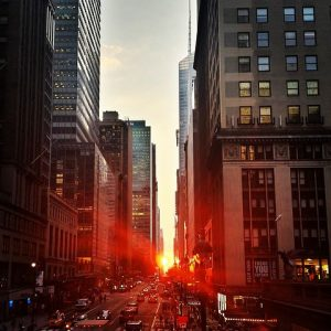 Red sun rays beaming through Manhattan buildings