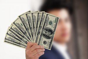 A man holding a lot of dollar bills.