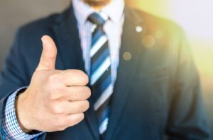 Man wearing black suit doing thumb up