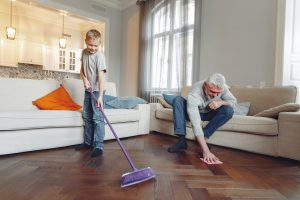 man and a boy cleaning a wood floor