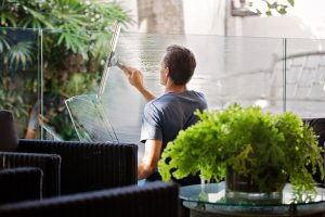 man cleaning glass wall