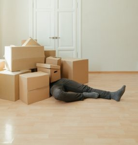 A person covered in moving boxes.