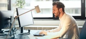 man smiling while typing - moving companies Eagleswood