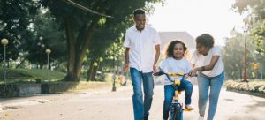 Mother and father teaching kid to ride a bike